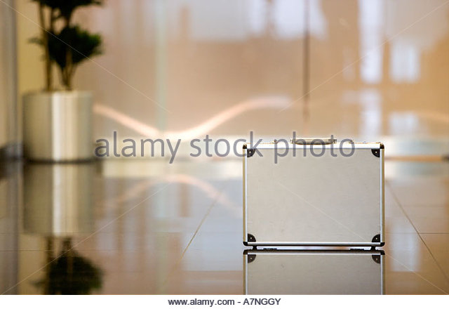 Reflection of silver briefcase on shiny lobby floor - Stock Image