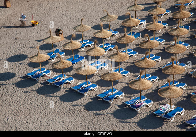 A man cleans the beach early in the morning, before bathers arrive, in Saint Elm, Mallorca, Spain - Stock Image
