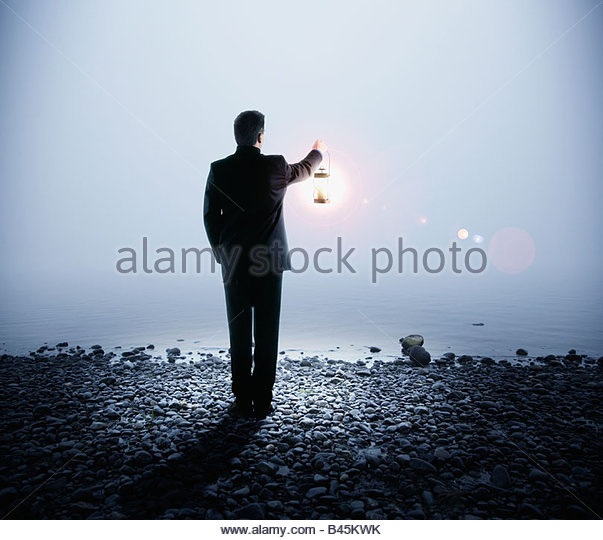 Portuguese businessman holding lantern next to water - Stock Image