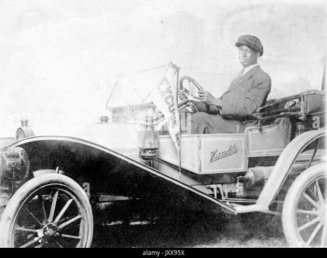 Three quarters shot of an African American man driving a Hupmobile, wearing a suit and hat, neutral facial expression, - Stock Image