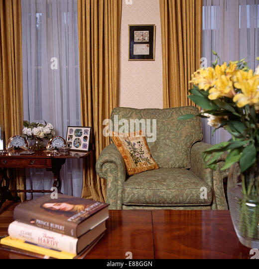 Green armchair and net curtains in archival living room - Stock Image