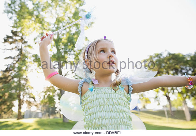Little girl wearing fairy costume outdoors - Stock Image