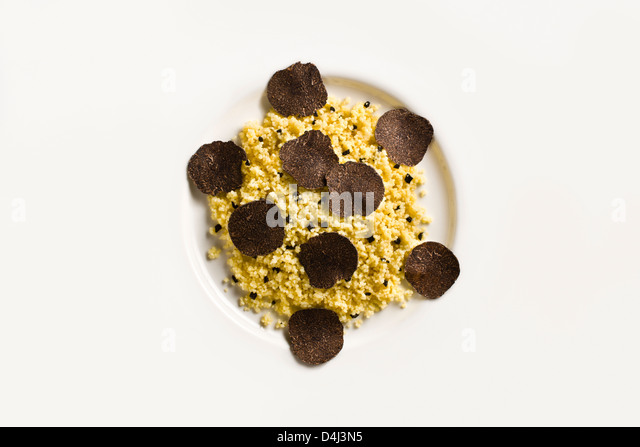 Cous Cous with Black Truffle on a white plate. - Stock Image