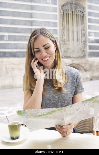 Young woman looking at map outside Museum of Ceramics, Valencia, Spain - Stock Image