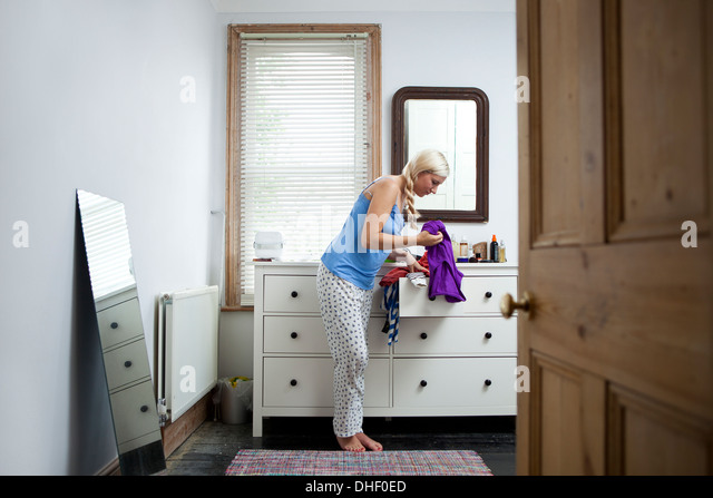 Young woman in bedroom deciding on outfit - Stock Image