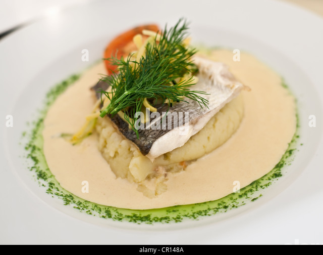 Close up of plate of fish and potatoes - Stock Image