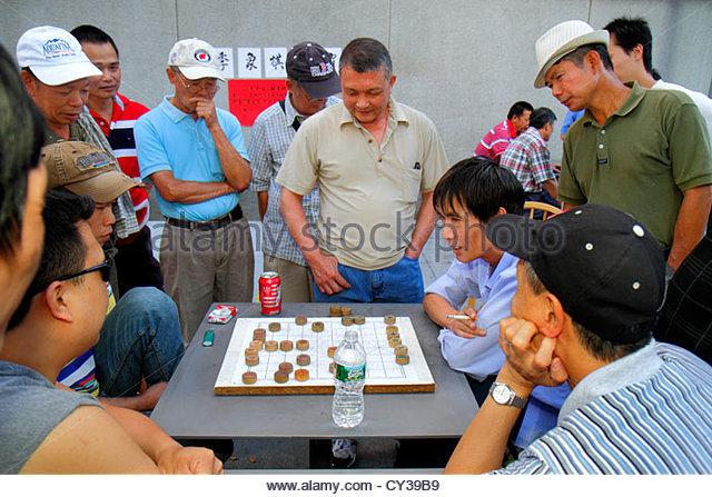 Boston Massachusetts Chinatown Chinatown Park Asian man playing game game board watching community - Stock Image