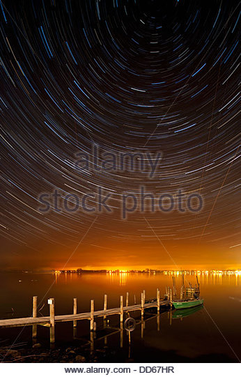 Germany, View of startrails above old jetty at night - Stock Image