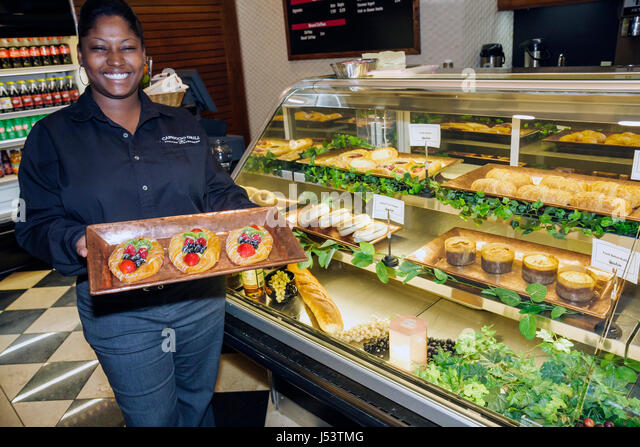 Little Rock Arkansas The Peabody Little Rock hotel Black woman bakery sweets tray fruit Danish counter attendant - Stock Image