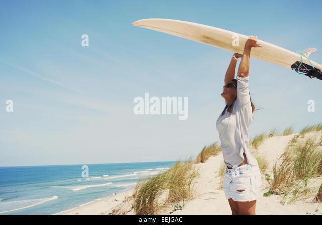 Woman with surfboard on beach, Lacanau, France - Stock-Bilder