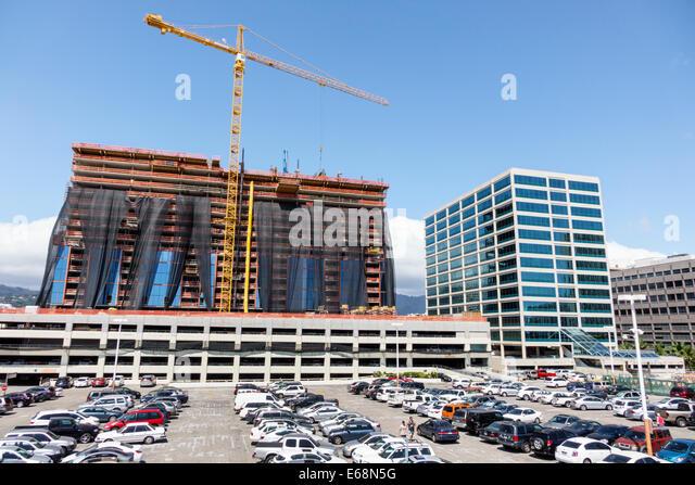 Hawaii Hawaiian Honolulu Ala Moana Center mall office building construction site crane parking lot parked cars economic - Stock Image
