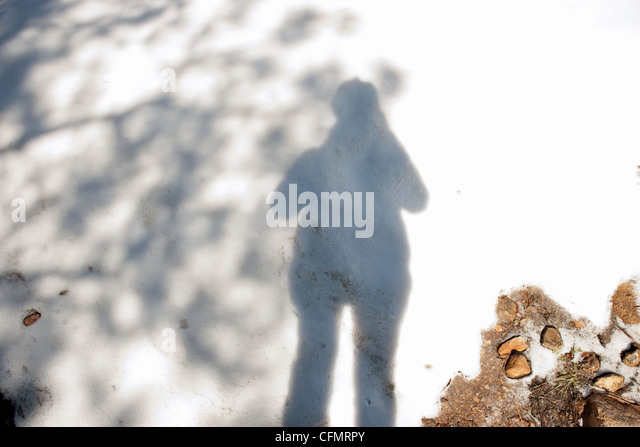 Shadow of photographer on snow. - Stock Image