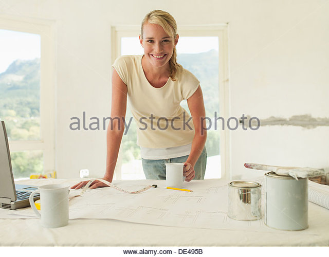 Smiling woman leaning on table with blueprints and paint - Stock Image