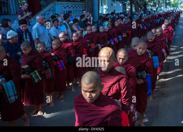 Mandalay Myanmar Burma Asia Parade attraction cue distributing food monastery monks pray religion tourists tradition - Stock Image