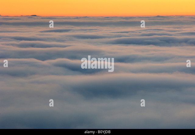 Banks of fog with sunset and horizon - Stock Image