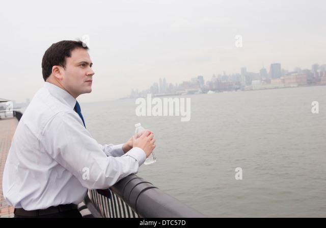 Businessman leaning on rail holding bottle of water - Stock-Bilder