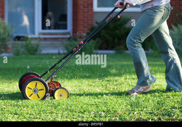 Woman cutting grass with an environmentally friendly lawn mower. - Stock Image