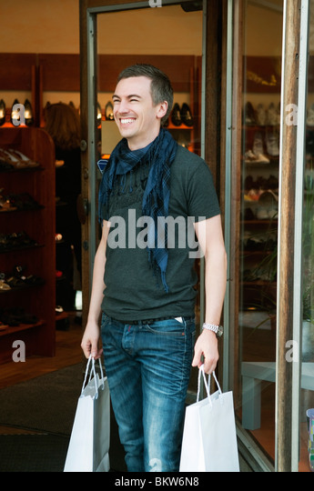 Happy man with shopping bags - Stock Image