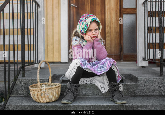 Sweden, Pensive girl (4-5) dressed up as Easter witch with Easter basket sitting on steps - Stock Image