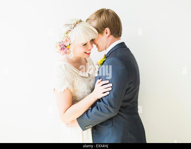 Smiling newlywed couple embracing - Stock Image