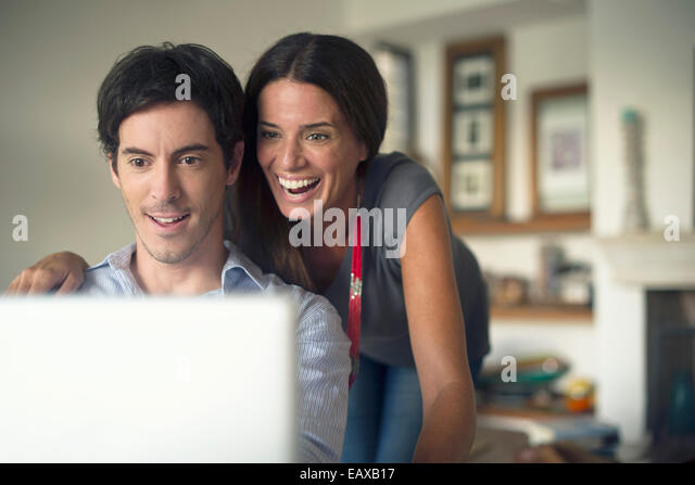Couple looking at laptop computer together - Stock Image