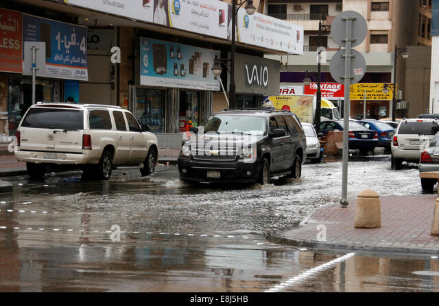 A car drives through the built-up rain water in the streets of Riyadh, Saudi Arabia - Stock Image