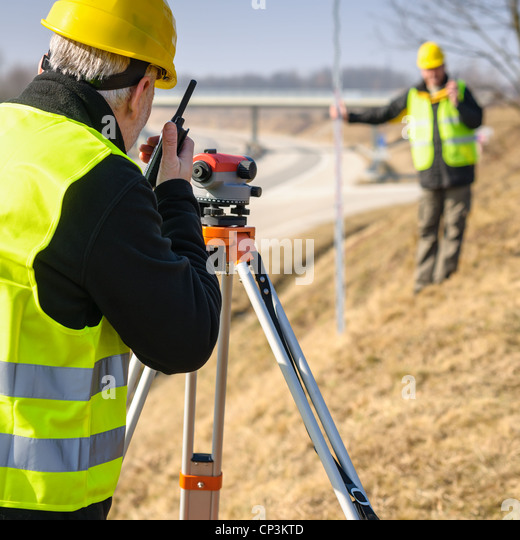 Land surveyors on highway measuring with theodolite - Stock Image