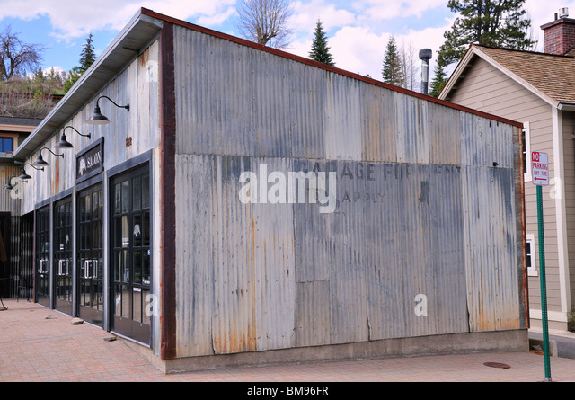 An old corrugated metal-sided building in Truckee which was restored and now houses a modern shop - Stock Image