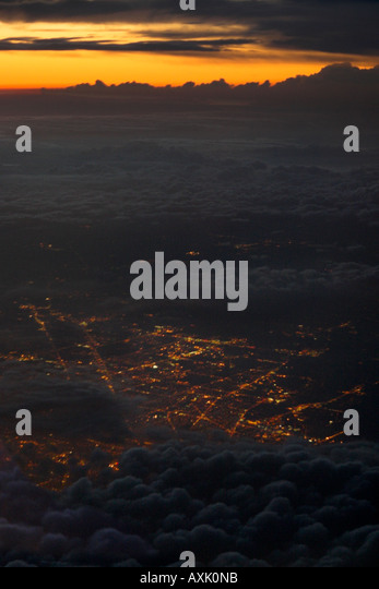 high up in sky above clouds heaven evening morning sunset sunrise down city urban culture grey orange lights roads - Stock Image