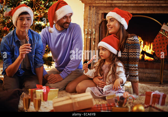 Young family relaxing by fireplace at home on Christmas evening - Stock Image