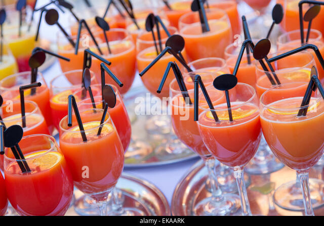a selection of non alcoholic fruit cocktail drinks served in glasses on silver trays - Stock Image