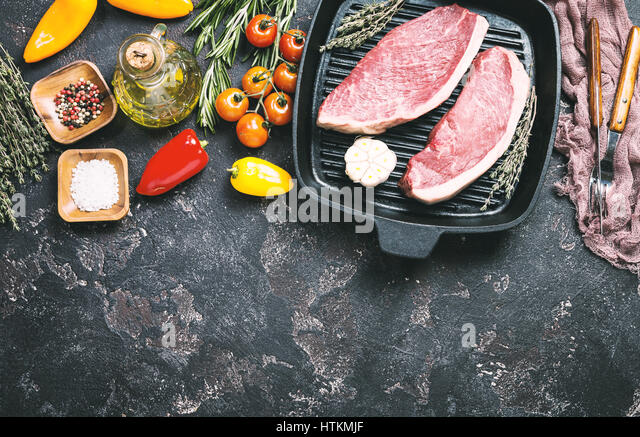 Fresh raw Prime Black Angus beef strip steaks on grill pan over dark rustic concrete background, top view. Ingredients - Stock Image