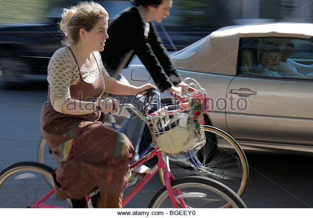 Charleston South Carolina Broad Street woman women young old car cyclist bicycle bike car basket exercise alternative - Stock Image