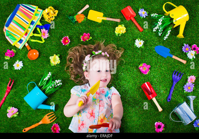 Kids gardening. Children with garden tools. Child with watering can and shovel. Little kid watering flowers - Stock Image