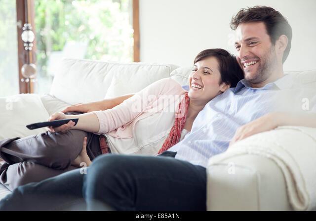 Couple watching TV together on sofa - Stock-Bilder