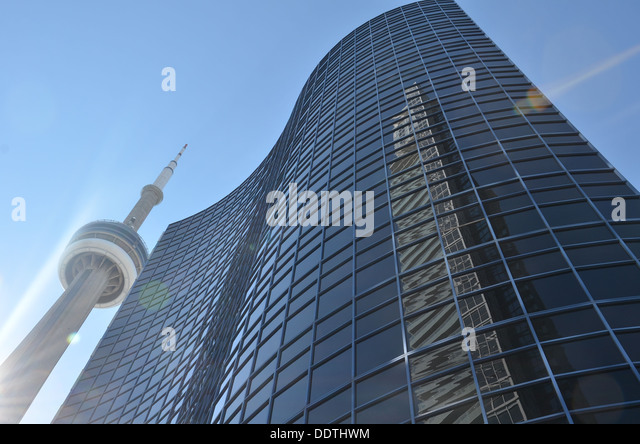 Looking up on a downtown walk towards the CN tower and viewing other buildings in the area as well as reflections. - Stock Image