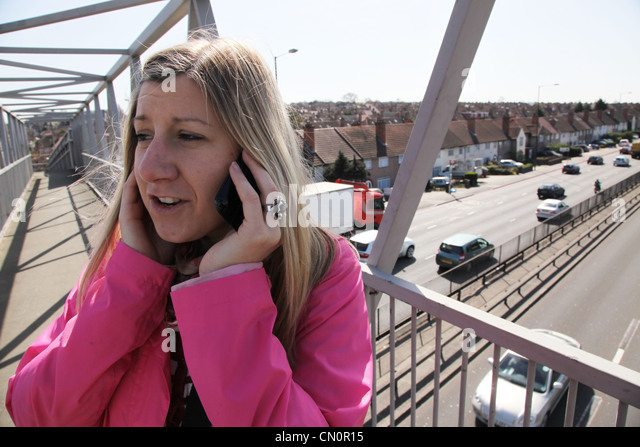 Woman talking on the phone above a noisy road, North Circular in Neasden, London - Stock Image