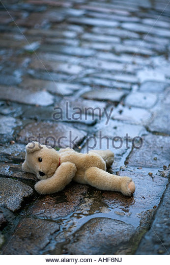 Abandoned teddy bear in wet gutter - Stock Image