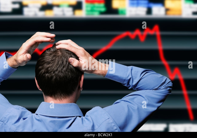 Stock Trader Clutching His Head in Front of a Screen Showing a Stock Market Crash - Stock Image