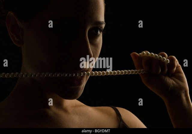 Woman holding string of pearls up to mouth, biting pearls, looking away - Stock Image