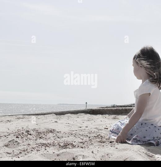 Girl sitting on the beach - Stock Image
