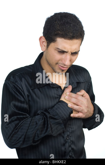 Young man hands over chest having a heartattack against a white background - Stock Image