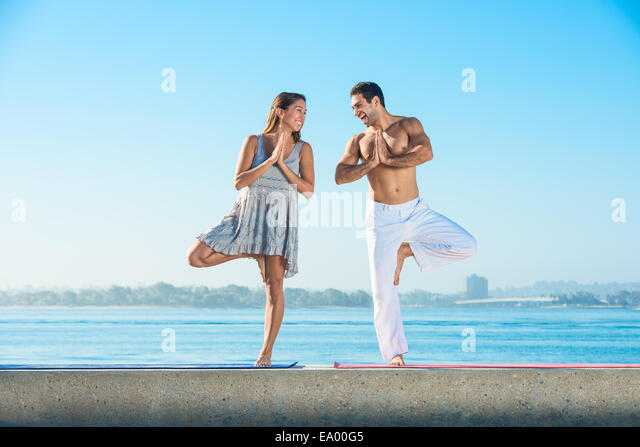 Young man and woman practicing yoga position on pier at Pacific beach, San Diego, California, USA - Stock Image