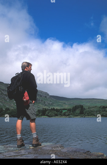 Ireland hiker standing at edge of lake - Stock Image