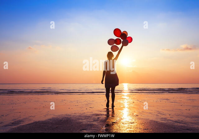 motivation or hope concept, follow your dream and inspiration, girl with balloons at sunset - Stock Image