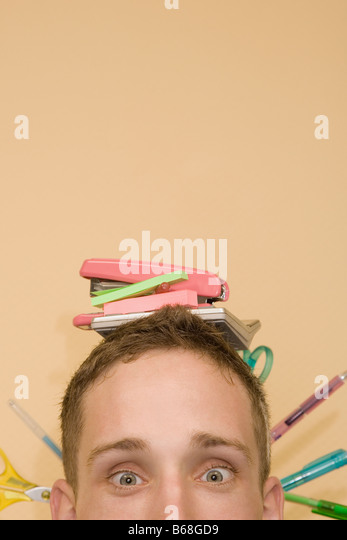 Close-up of a young man with stationery objects on his head - Stock Image