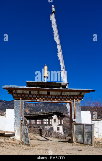 Monastery entrance gate framing village house, Ura, Bumthang, Bhutan - Stock Image