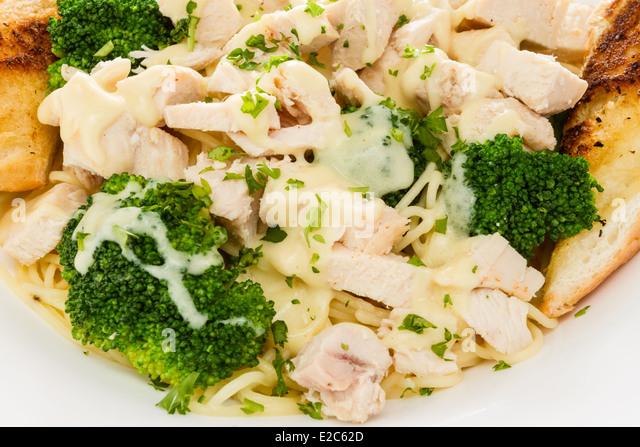 Chicken alfredo with pasta, broccoli, and garlic bread. - Stock Image