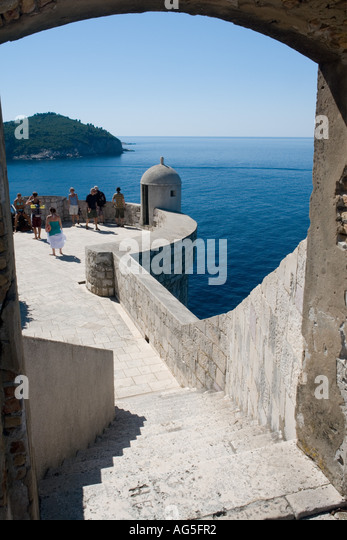 Old city defensive walls in Dubrovnik in Croatia, image includes tourists - Stock Image