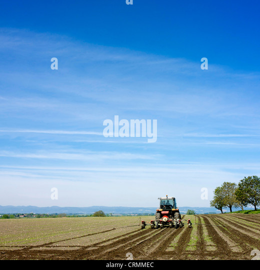 Tractor plowing a field in France, Europe. - Stock Image